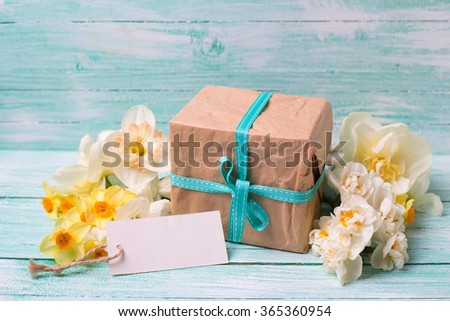 Present box,  flowers  and empty tag on turquoise painted wooden background. Place for text. Selective focus. - stock photo
