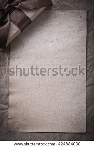 Present box with bow sheet of wrapping paper holidays concept. - stock photo