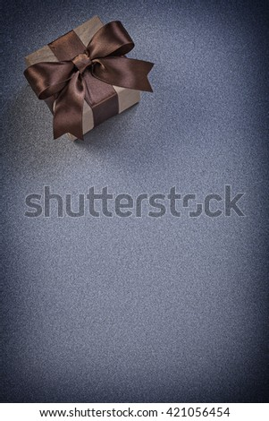 Present box with brown bow on grey background celebrations concept. - stock photo