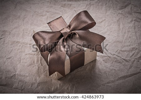 Present box with brown ribbon on wrapping paper holidays concept.