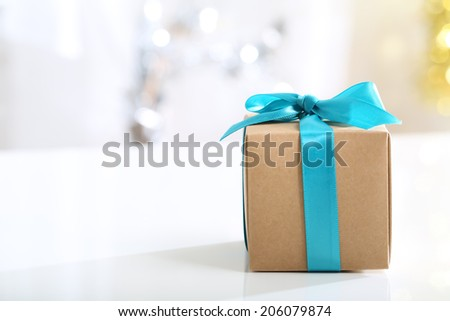 Present box with teal bow in a bright room - stock photo