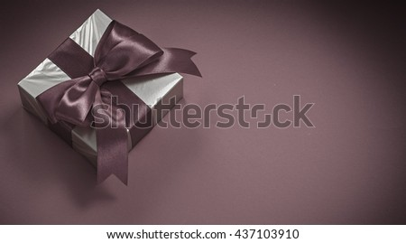 Present box with tied bow on red background holidays concept. - stock photo