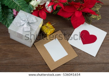 Present boxes with paper card and Christmas leaf on table.