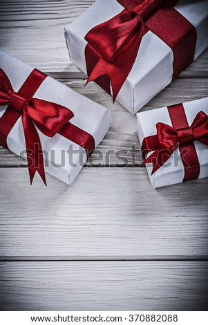 Present boxes with tied ribbons on wooden board holidays concept.