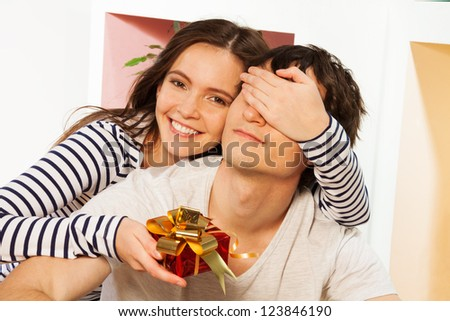 Present for him on the lovers Valentine's day, woman giving small present in red box to man - stock photo