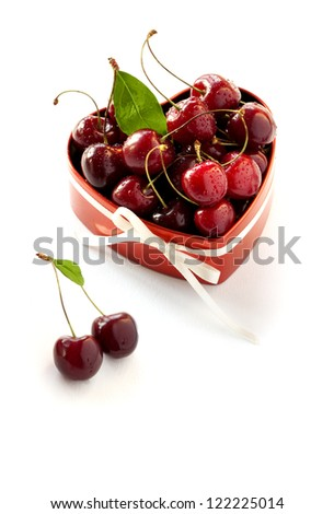 Present for Valentine's day. Red heart shaped box with sweet cherries and white ribbon. Isolated on white background.