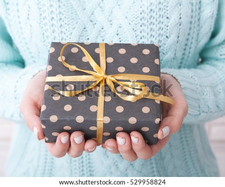 Present. Gift bos. Woman holding small gift box with ribbon.