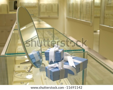 Present gift in jewerly shop. Blue boxes for jewerly near the mirror - stock photo