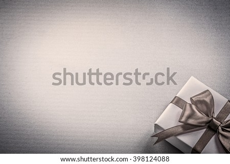 Present red bow on blue background greeting card holidays concept. - stock photo