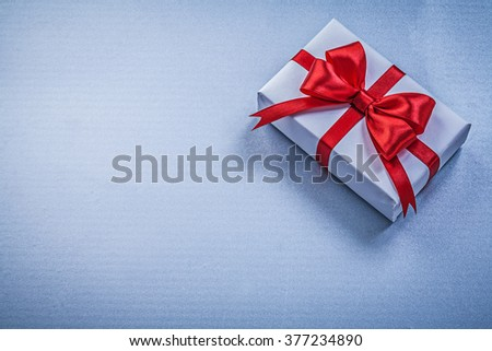 Present with ribbon on blue background holidays concept. - stock photo