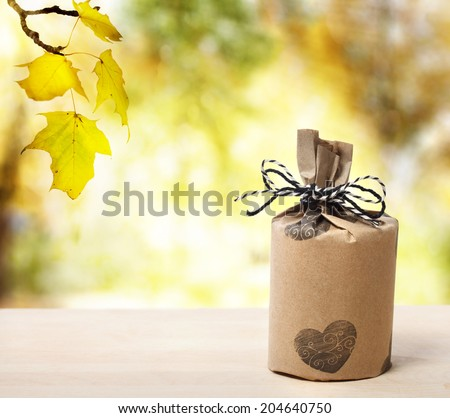 Present wrapped in a rustic earthy style over yellow forest - stock photo
