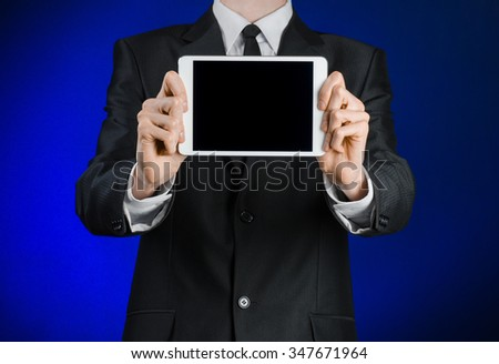 Presentation and business theme: a man in a black suit holding a white tablet touch computer gadget with touch blank black screen on a dark blue background in studio isolated - stock photo