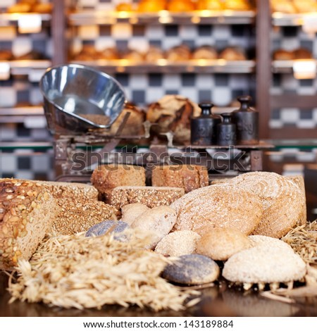 Presentation of a large variety of loaves of bread and rolls in the bakery with a large scale for selling by weight on the counter behind - stock photo