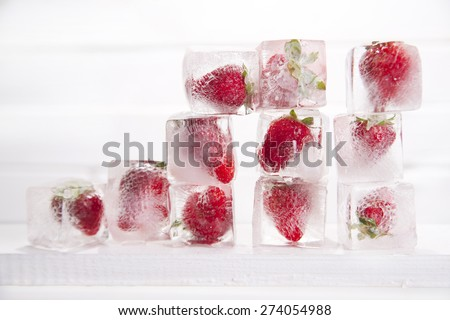 Presentation of a series of ice cubes with strawberries - stock photo
