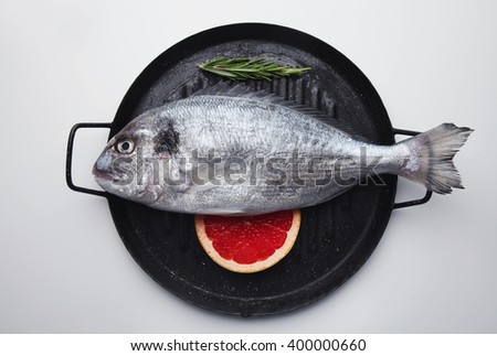 Presentation of fresh sea bream on grill pan ready to cook, isolated in center of white table with grapefruit slice below and rosemary herb spice above, top view. - stock photo