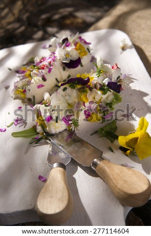 Presentation of goat cheese rolls with edible flowers