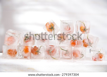 Presentation of ice cubes inside with grains of tomato Pachino - stock photo