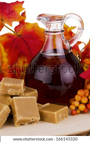 Presentation of maple syrup and sugar cream on wooden plate. - stock photo