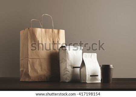 Presentation of retailer package set: craft paper bag, big pouch, small container and take away glass with cap. Filled with goods, blank labeled, merchandise pack - stock photo