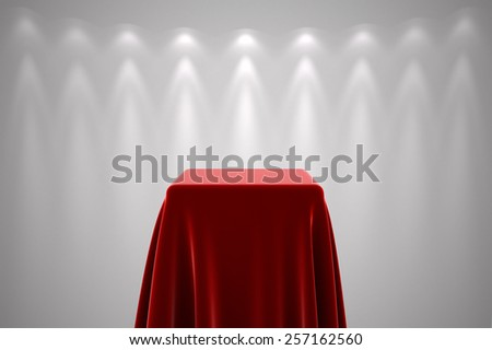 Presentation pedestal covered with a red silk cloth in front of a white wall illuminated by spot lights - stock photo