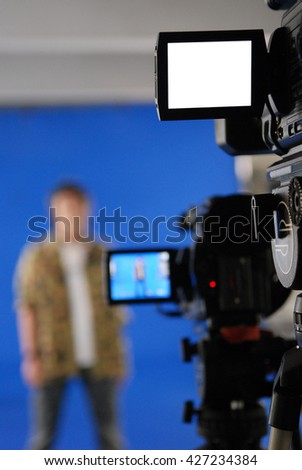 Presenter on blue screen.Focusing on some of the camera