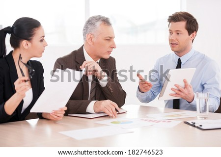 Presenting his ideas. Three confident business people discussing something while sitting at the table