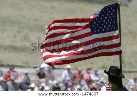 Presenting the colors (American Flag) to a rodeo crowd before the start of action (shallow focus).