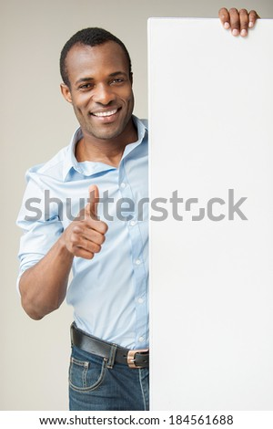 Presenting your product. Cheerful African man in blue shirt leaning at copy space and showing his thumb up while standing against grey background - stock photo