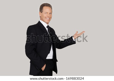 Presenting your product. Cheerful mature man in formalwear pointing away and smiling while standing against grey background
