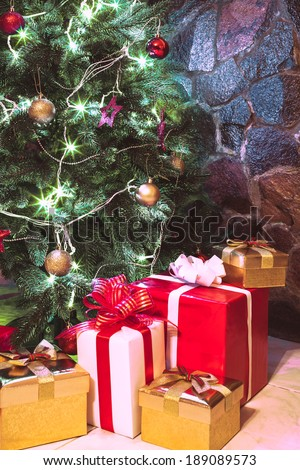 Presents boxes under the Christmas tree. Gold, red and white colours