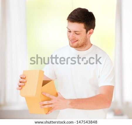 presents, gifts and celebration - man in white t-shirt with gift box - stock photo