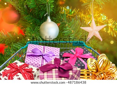 presents ribbon gift box in shopping trolley cart with christmas tree decorations background.
