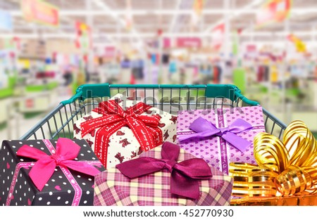 presents ribbongift box in shopping trolley in shopping mall. - stock photo