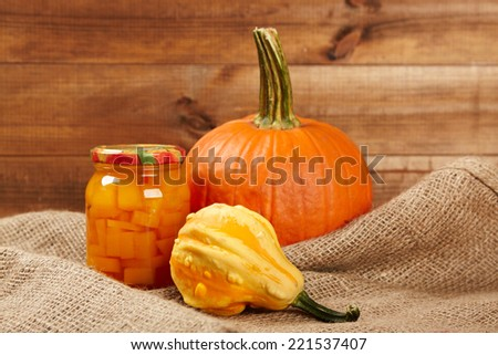 Preserved autumn vegetables on shelf in wooden wall