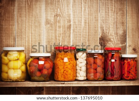 Preserved  autumn vegetables on shelf near a brown wooden wall - stock photo