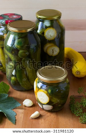 Preserved cucumbers and other vegetables in glass jars. Traditional Russian appetizer
