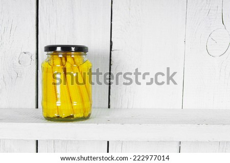 Preserved food in glass jar, on a wooden shelf. Marinaded corn - stock photo
