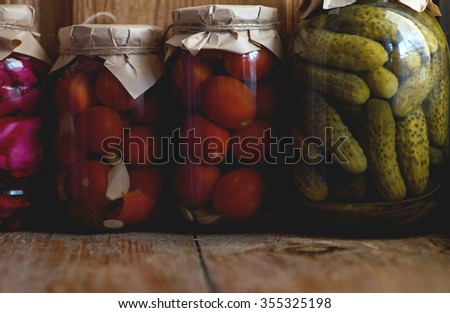 Preserved food in glass jars, on a wooden shelf. Various marinaded food - stock photo