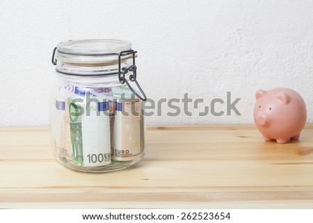 preserving glass with Euro banknotes and a piggy bank on a wooden board, financial concept for saving money - stock photo