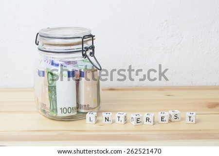 preserving glass with Euro banknotes and letter cubes with word interest on a wooden board, financial concept for saving money and interest - stock photo