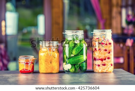 Preserving. Pickles jars. Jars with pickles, pumpkin dip, white cabbage, roasted red yellow pepper. Pickled Vegetables. Vegetable being prepared for preserving. Toned image. - stock photo