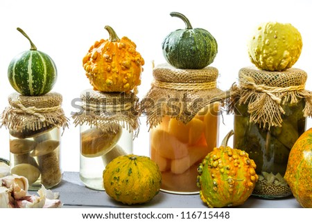 Preserving small pumpkins and mushrooms in the basement - stock photo