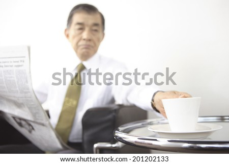 President having a cup of coffee while reading a newspaper