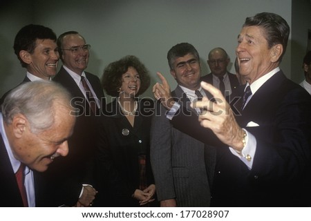 President Ronald Reagan jokes with politicians and reporters and tells a joke.