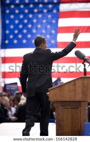Presidential Candidate Barack Obama waves to crowd as he is framed against American Flag at early vote for change Presidential rally October 29, 2008 at Halifax Mall, Government Complex in Raleigh, NC - stock photo