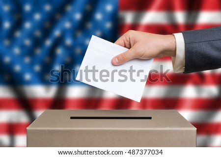 Presidential election in United States of America. The hand of man putting his vote in the ballot box. American flag on background.