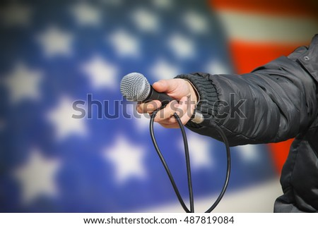 Presidential election survey. Hand holding microphone against an american flag asking about preferred government