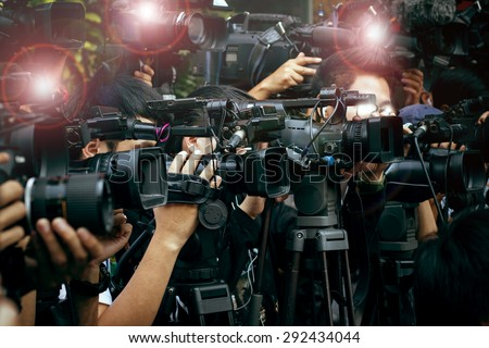 press and media camera working on public news coverage event - stock photo