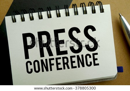 Press conference memo written on a notebook with pen - stock photo