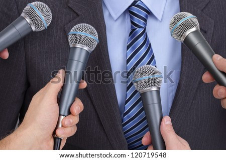 Press conference with media microphones held in front of business man, spokesman or politician - stock photo